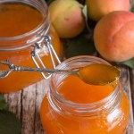 apricot jams in 2 jars with a spoonful of jam on the rim