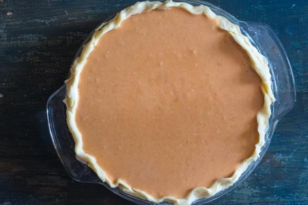 Pumpkin pie filling in crust ready for baking
