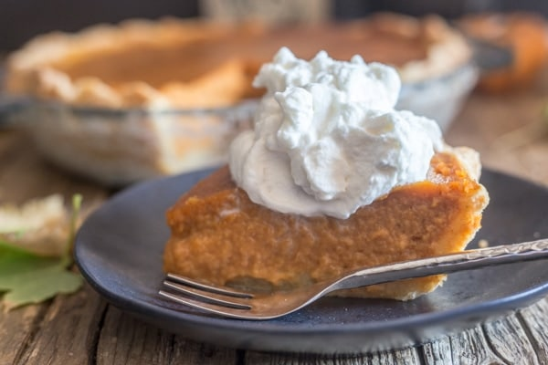 slice of pumpkin pie and maple whipped cream on a black plate