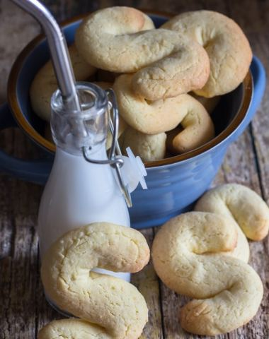 s cookies in a bowl and one leaning against a bottle of milk