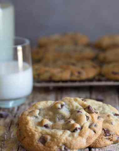 chocolate chunk cookies on a board with a glass of milk