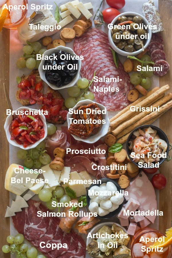 all the ingredients written for an antipasto cheese board