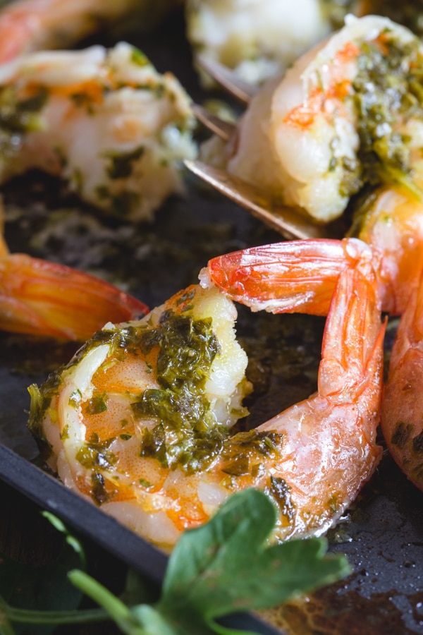 baked shrimp with a parsley sauce on a white plate