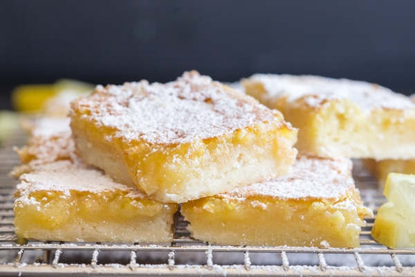lemon squares on a wire rack dusted with powdered sugar