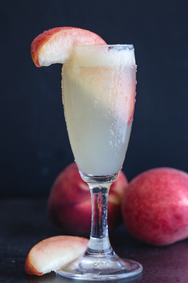bellini cocktail in a flute glass with a slice of peach