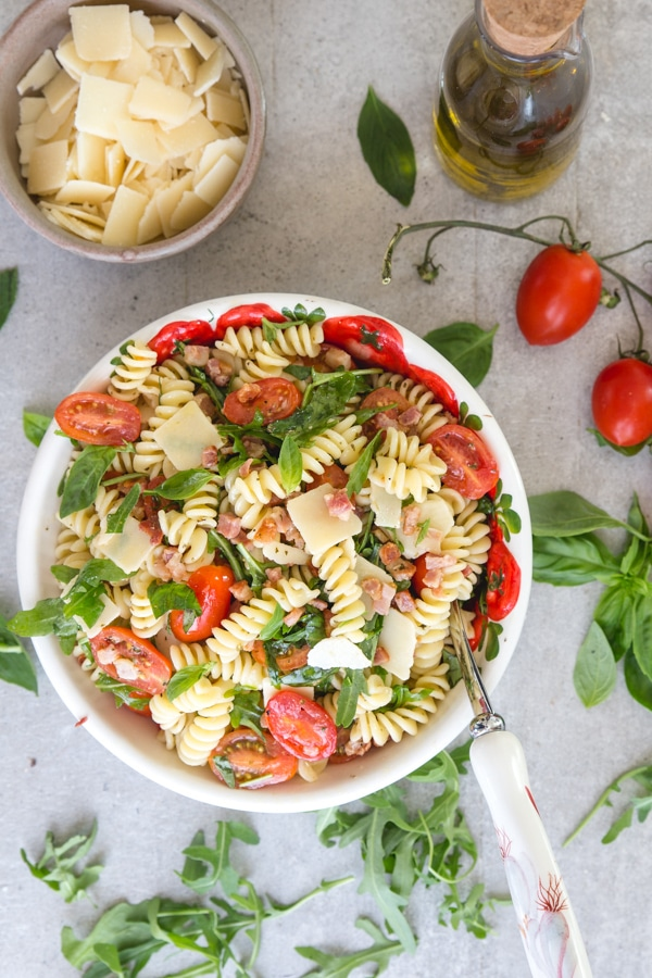 pasta salad on a white board with parmesan flakes in a bowl and olive oil and tomatoes