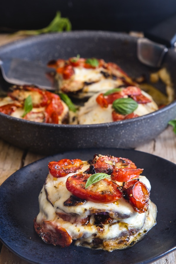 eggplant parmesan stacks in a pan and one on a black plate