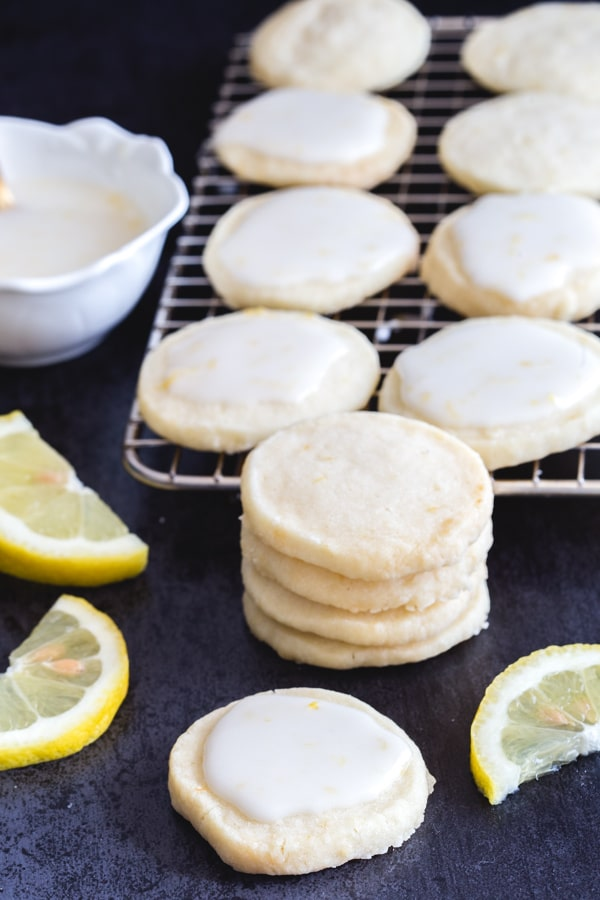 lemon cookies stacked and on a wire rack