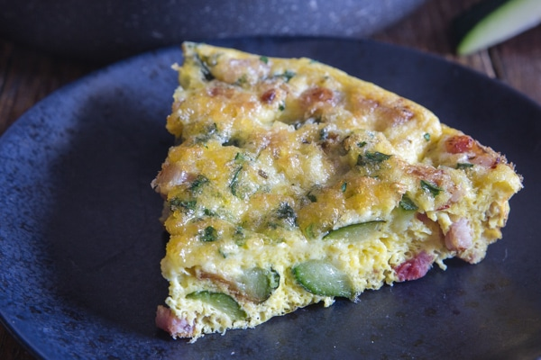 up close slice of baked frittata on a black plate