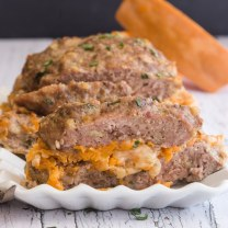 sliced stuffed meatloaf on a white dish