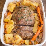 stuffed meatloaf in a white pan with potatoes and carrots