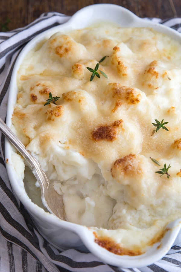 cauliflower casserole in a white baking dish with fresh thyme on top