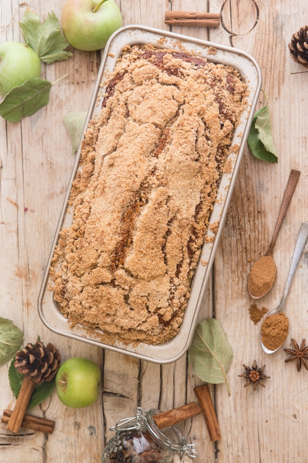 applesauce bread on a wooden board with apples and spices