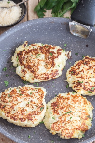 cooked cauliflower fritters in a frying pan browned on both sides