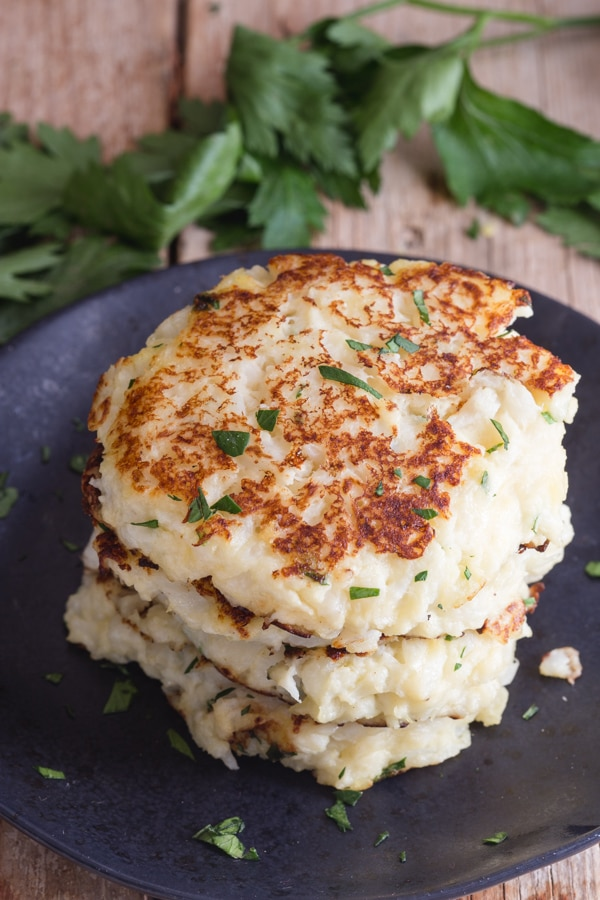 cauliflower fritters on a black plate with fresh parsley