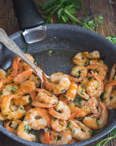 sauteed shrimp with parsley in a black frying pan and a silver spoon