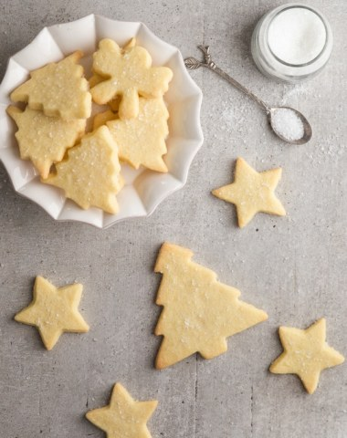 sable cookies on a grey board and some in a white plate with sugar on a spoon and in a jar