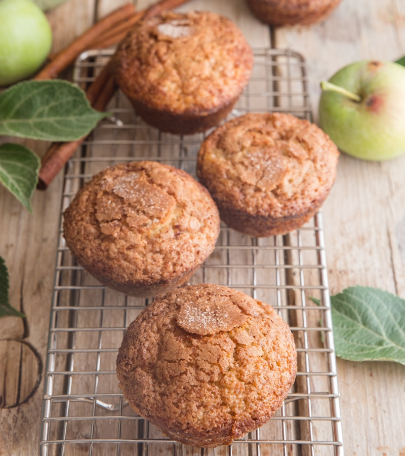 applesauce muffins on a wooden board with applesauce in a container and apples