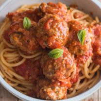 3 meatballs on a bowl of spaghetti with basil leaves on top