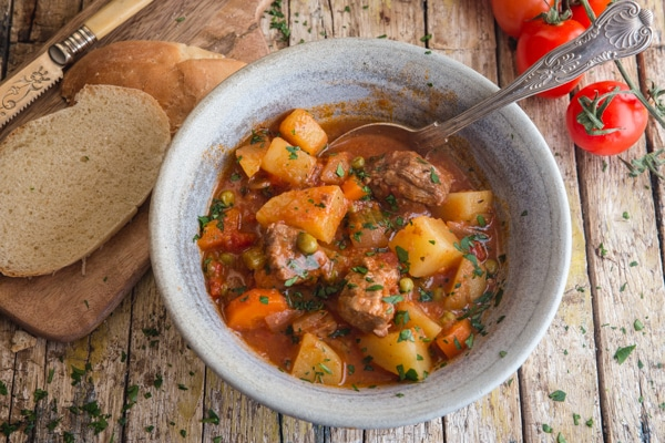 beef stew in a blue bowl with slices of bread and fresh tomatoes in the background