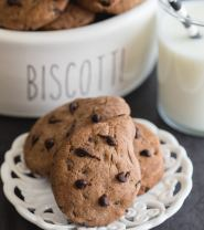 gocciole on a small plate with a glass of milk and a black and white straw and cookies in a biscotti container