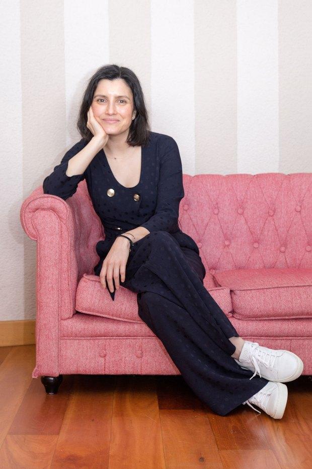 """Maria Cunha, CEO das Josefinas, vestida de preto com ténis brancos """"Josefinas"""", sentada num sofá rosa."""