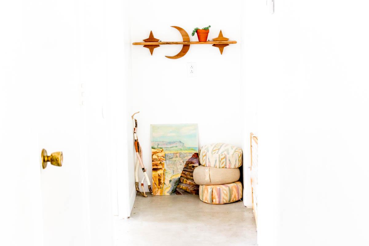 desert inspired hall way rug poufs art work shelves
