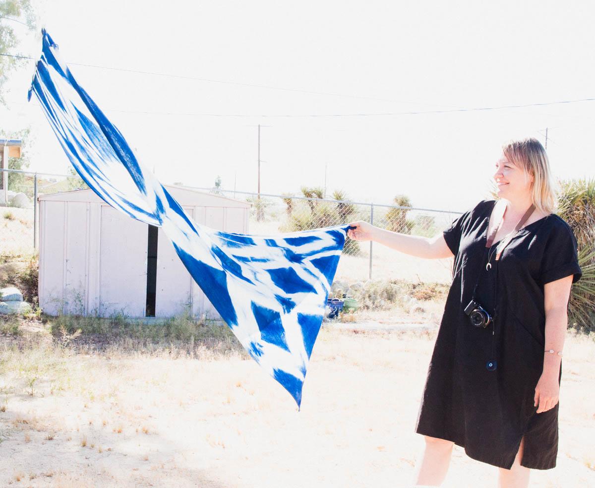 Lindsay Hollinger holding up shibori dye textile