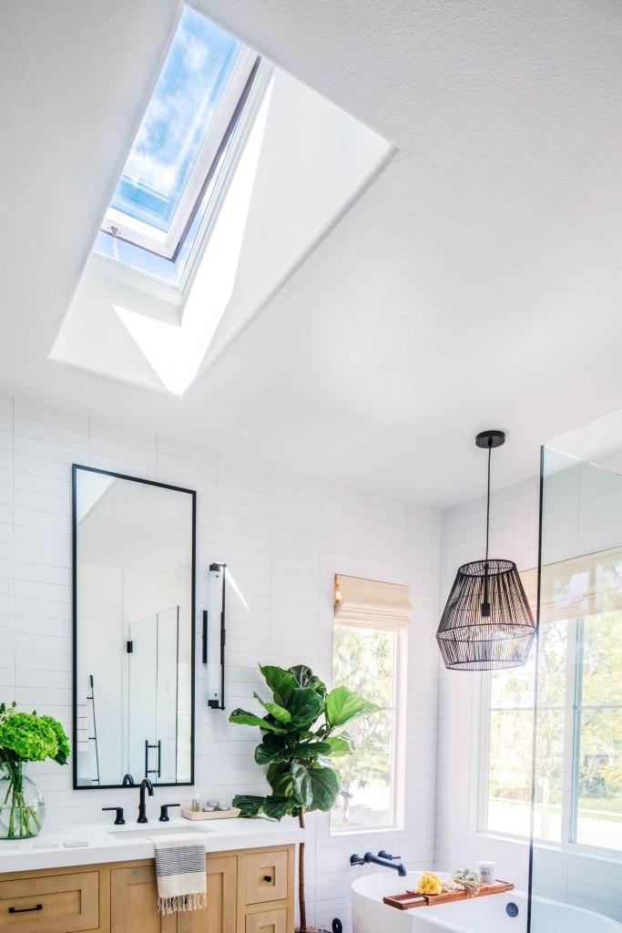 master bathroom Velux skylight black pendant free standing tub white oak vanity