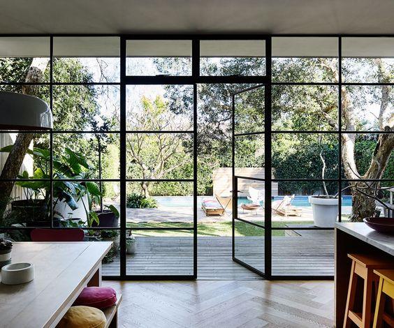 Black framed windows from kitchen to back yard