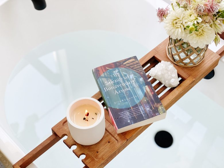 A candle burning on the bathtub caddy beside a vase of flowers