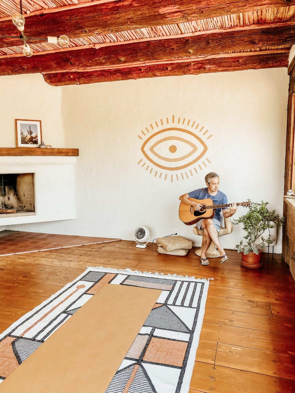 Travis playing guitar in an open yoga room beneath a minimalist mural of an eye