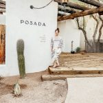 Anita on a rustic porch, beside the sign for the Posada