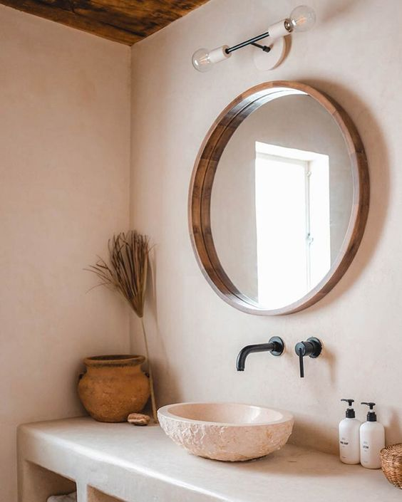Earthen vessel sink set below a round wooden mirror with black matte faucet and fixtures