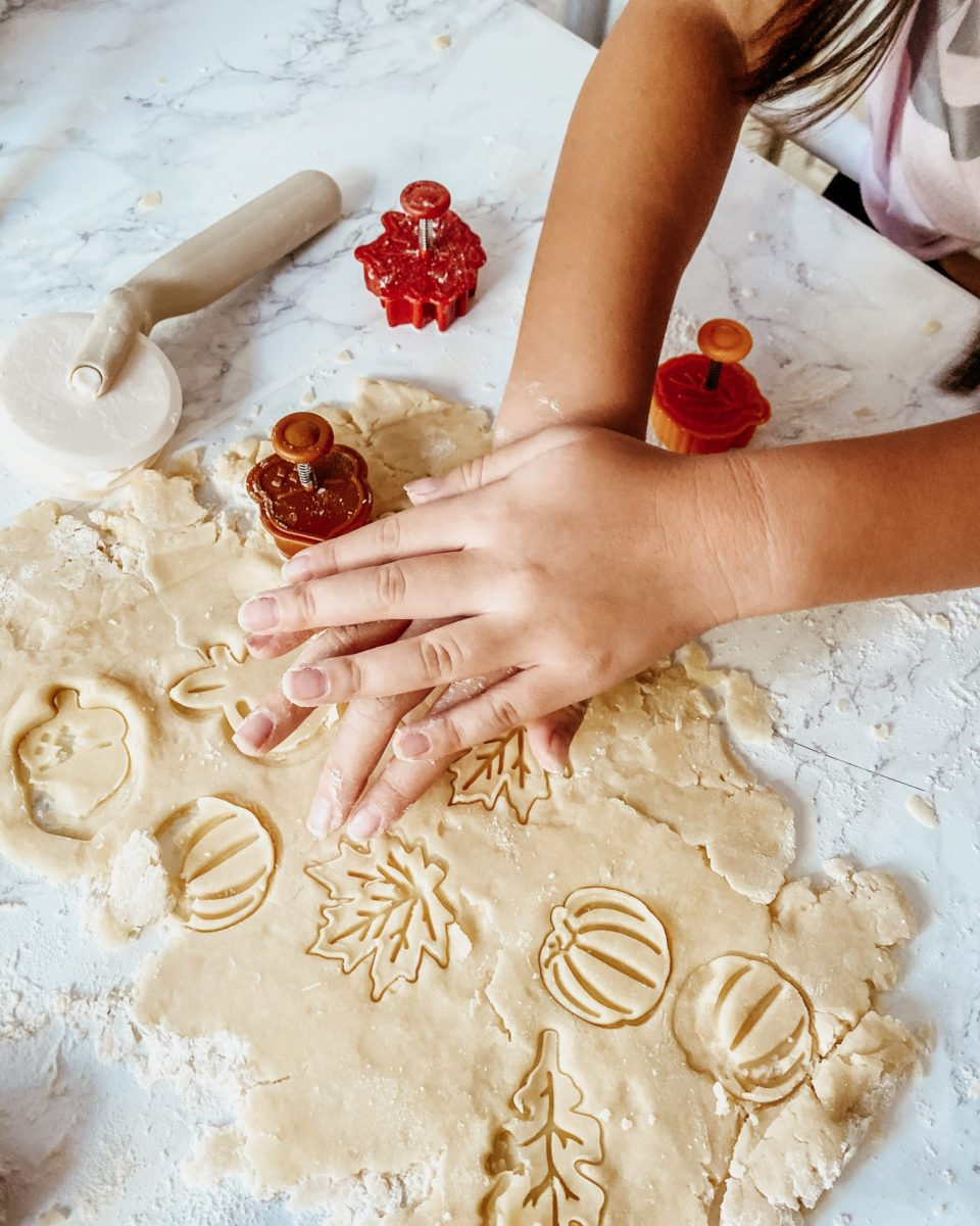 Natalie's teeny hands cutting fall shapes (leaves, pumpkins) into pie dough