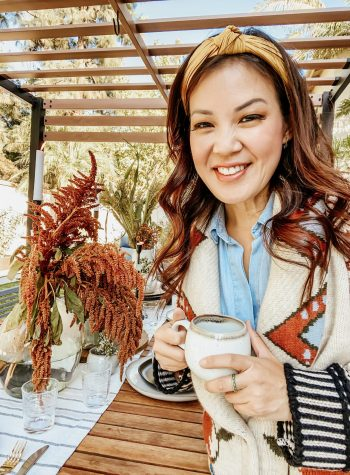 Anita wears a chunky, knit sweater holding a mug, standing in front of her completed tablescape
