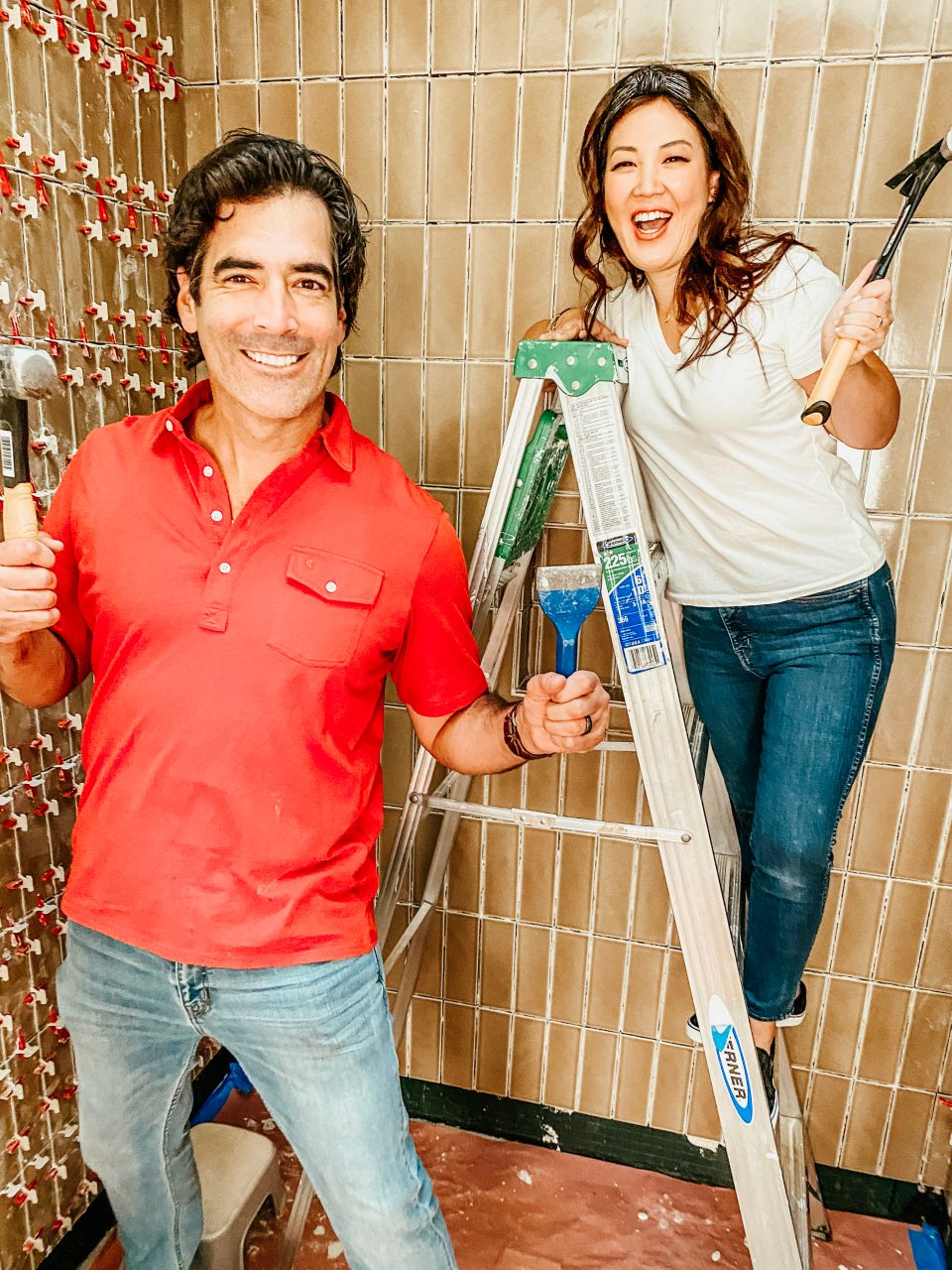 Anita & Carter pose with tools in the tiled shower