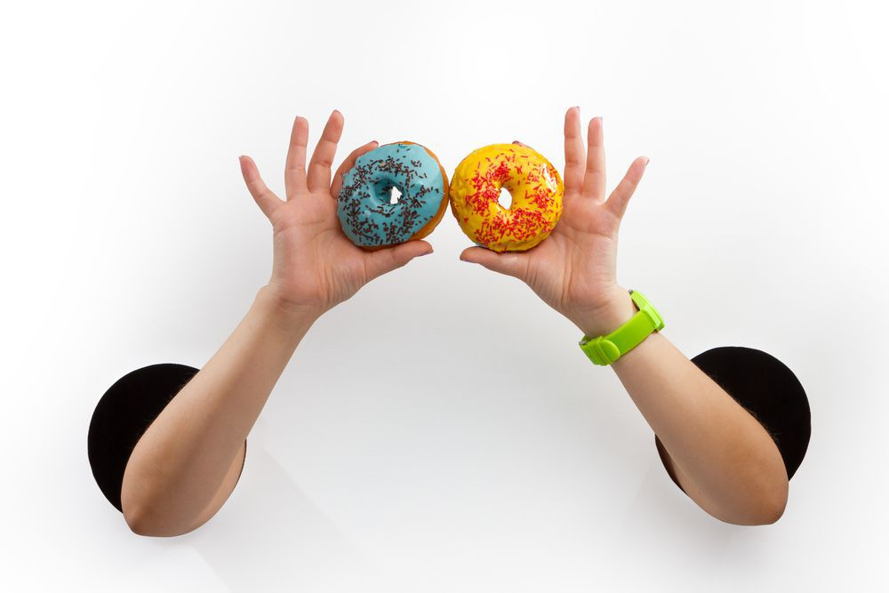 Female  hands through the holes on a white background are holding glazed donuts; Shutterstock ID 483536773; PO: redownload; Job: redownload; Client: redownload