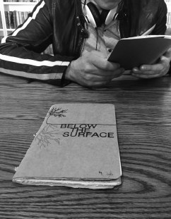 Black and white photo showing a sketchbook on the table and a man on the other side of the table looking at a sketchbook.