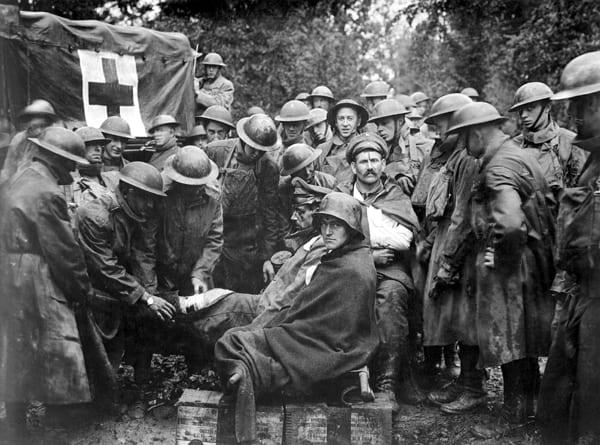 Verwundete deutsche Gefangene, die britischen Soldaten medizinisch versorgt werden, circa September 1918.