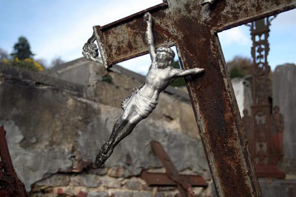 Foto einer beschädigten Christus-Figur, die an einem rostigen Kreuz hängt