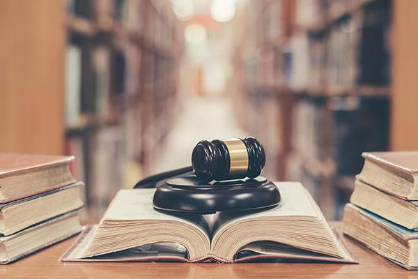 Bibliothek mit Buch und Richterhammer im Vordergrund