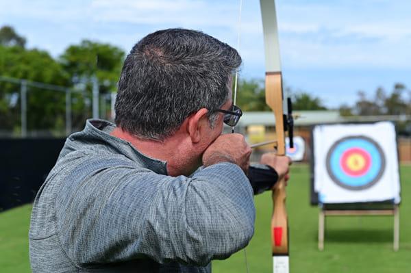 Alter Mann, der mit Bogen auf Zielscheibe zielt
