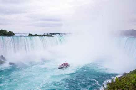 splashing niagara falls and yacht sailing on river