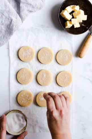 overhead shot of a person sprinkling sugar on cookies