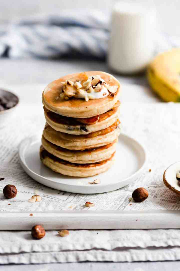 side view of stack of 5 pancakes topped with chopped hazelnuts