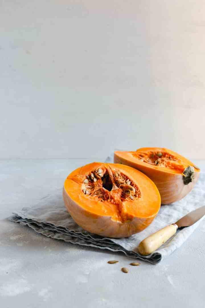 Pumpkin cut in half on a kitchen surface