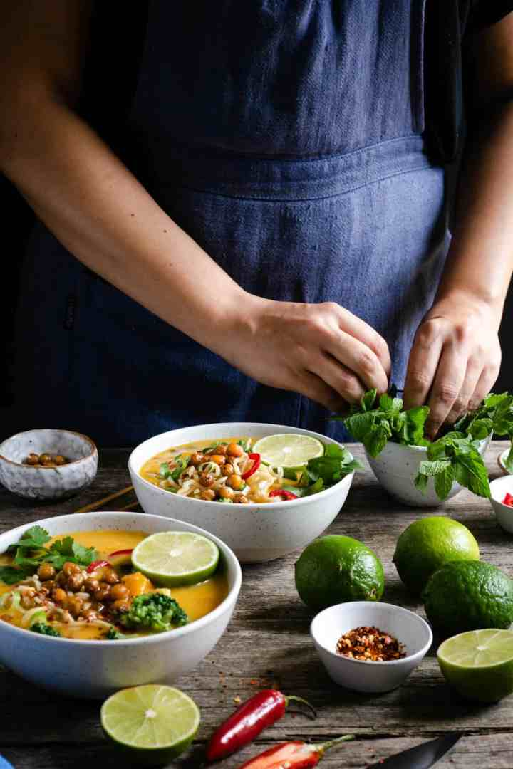 A person topping up two bowls of Thai style pumpkin laksa with fresh mint