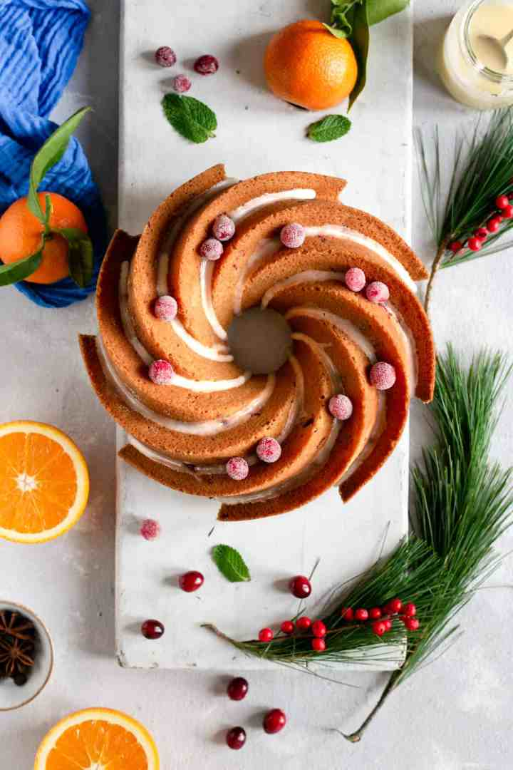 An overhead shot of a whole orange and cranberry cake with drizzle