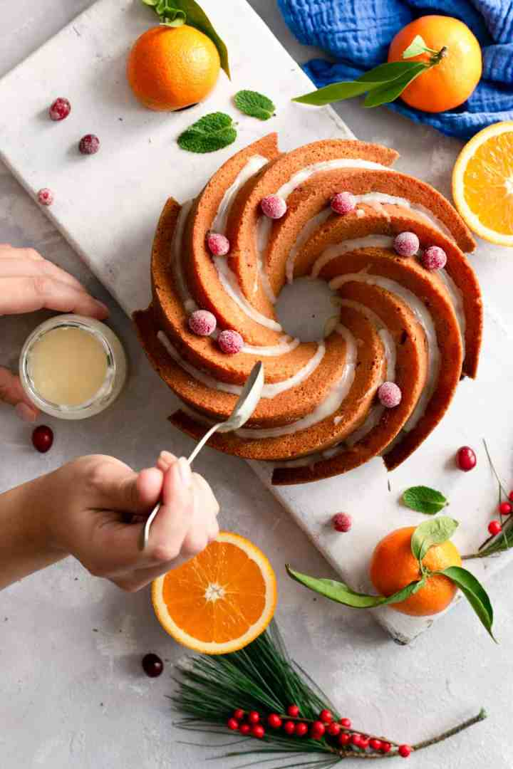 Overhead shot of a person drizzling orange and cranberry bundt cake with some icing